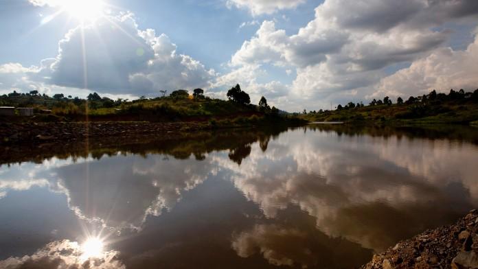 Sonne und Wolken spiegeln sich auf einer Flußlandschaft