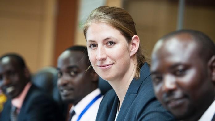 Eine Frau am Tisch mit Afrikanern.