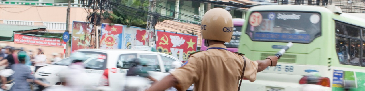 A police officer regulates traffic in an Asian city