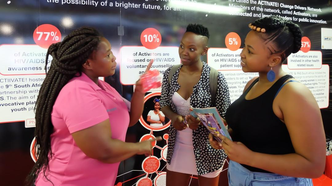 Junge Afrikanerinnen unterhalten sich auf einer Messe