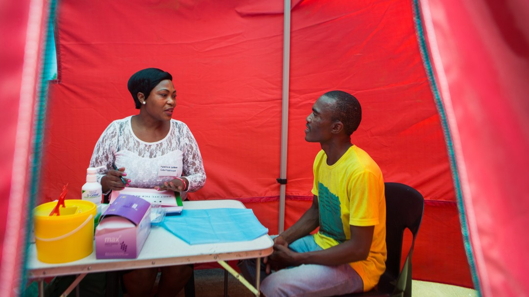 A nurse performs an HIV test and advises clients.