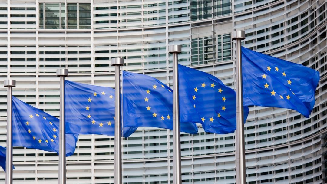 Europaflaggen wehen an Fahnenmasten vor einem Gebäude