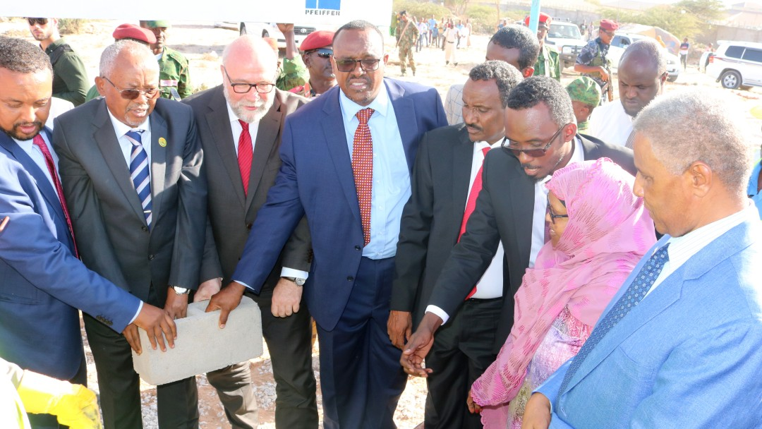 8 people, politicians and the CEO of Hargeisa Water Agency symbolically lay the foundation stone for their common programme.
