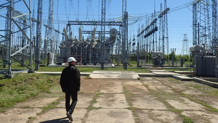 Man in front of power grid