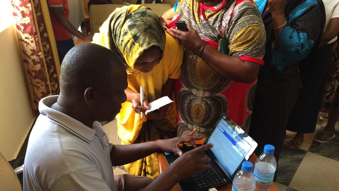 Viele Frauen stehen Schlange, um am Laptop die digitalen Lösungen gezeigt zu bekommen