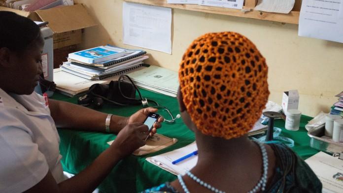 Eine Ärztin verwaltet die Gesundheitsversorgung einer Patientin mit dem Handy.