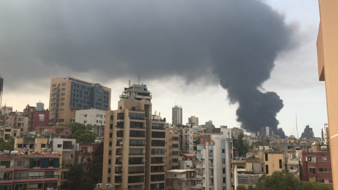 View over the skyscrapers of the city of Beirut shows the big dark explosion cloud.