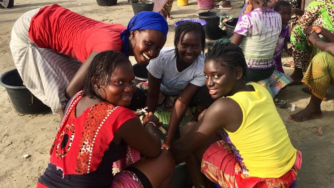 Junge Frauen sitzen auf Eimern am Strand