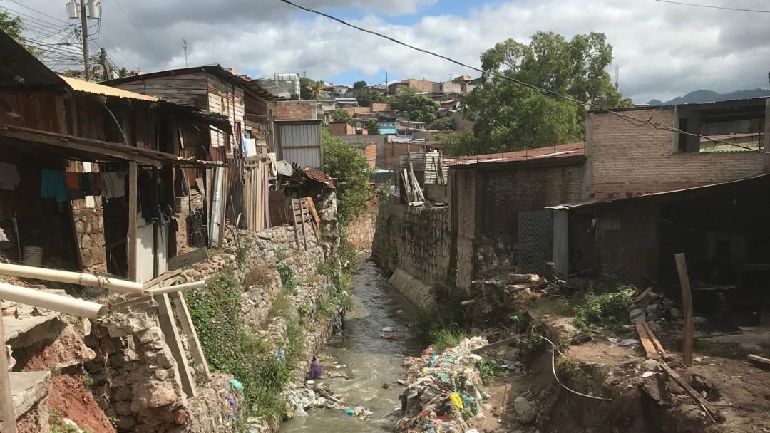Müll in einem kleinen Bach, der durch die Wellblechhütten eines Slums führt