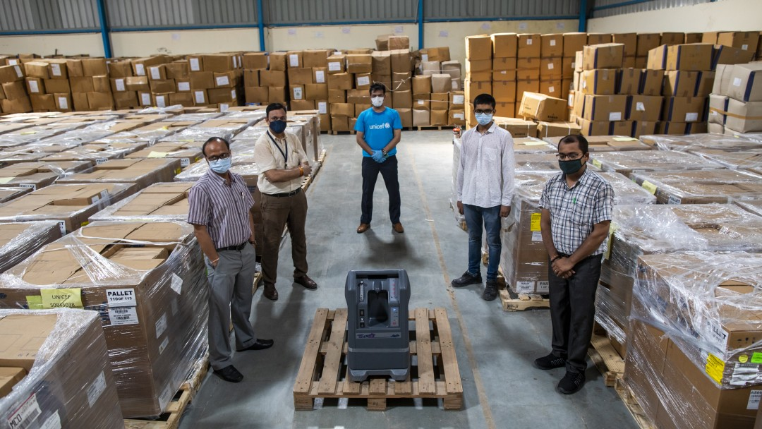 Mehrere Männer stehen in einem Lagerraum voller Kartons