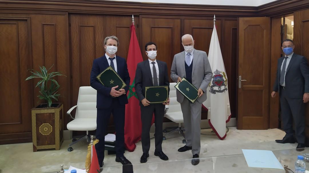 drei Männer stehen nach der Vertragsunterzeichnung zusammen, sie tragen alle eine Maske.