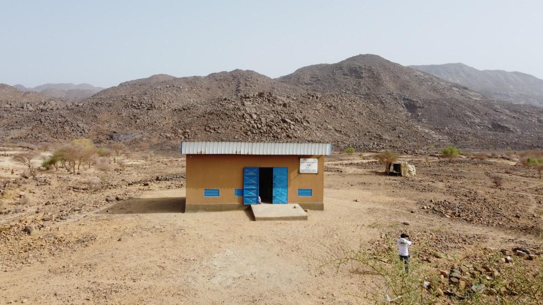 Kleines Haus in wüstenartiger Umgebung mit viel Sand