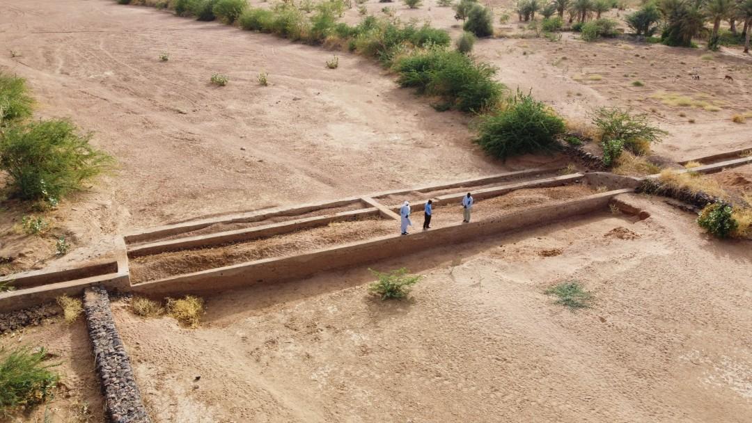 Ausgetrocknetes Flussbett mit Damm auf dem drei Männer stehen