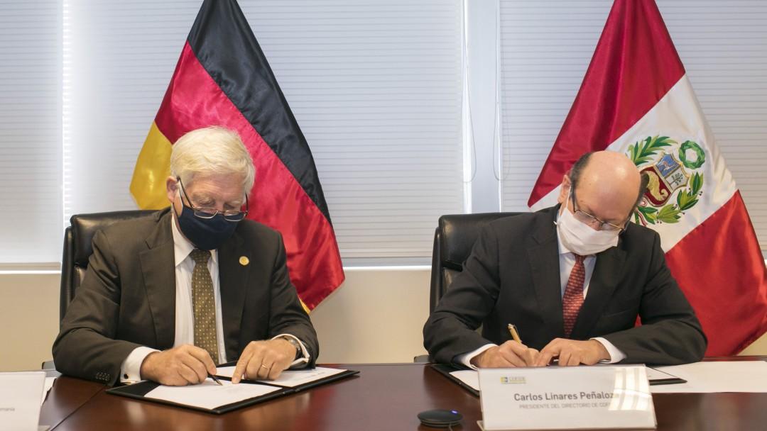Beide Personen tragen eine Maske und sitzen am einem Tisch für die Unterzeichnung