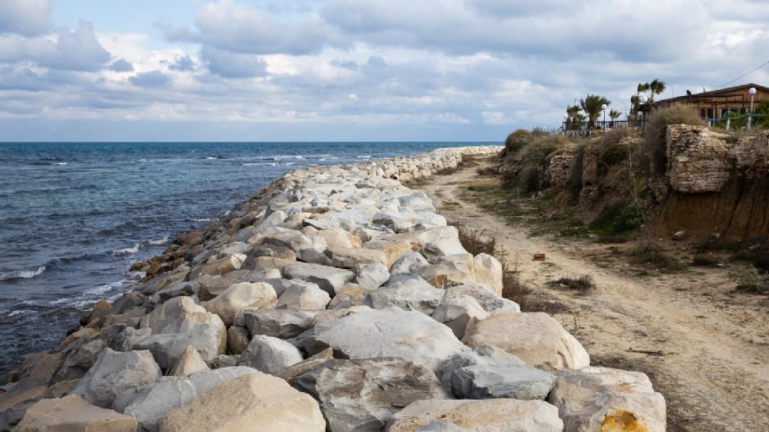 Küstenweg in Tunesien, der durch Wellenbrecher in Form von Felsen vom Meer getrentt ist.
