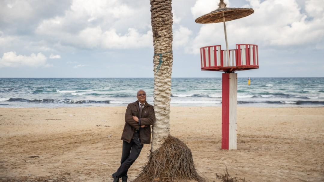 Ingenieur Mohammed Ali Torki steht am Strand, angelehnt an eine Palme.