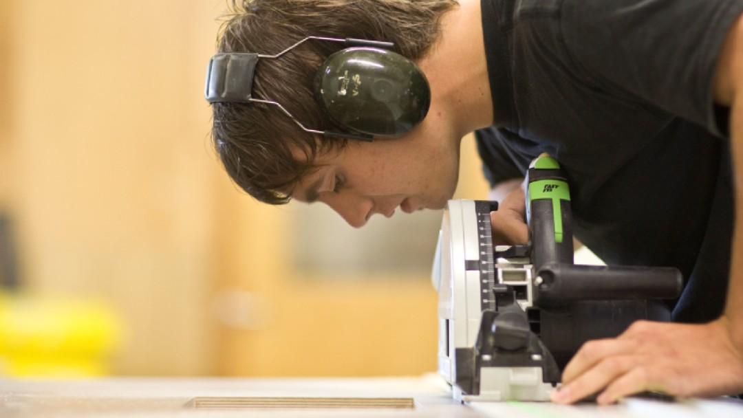 Ein junger Mann, der Schallkopfhörern trägt, arbeitet an einer Schleifmaschiene