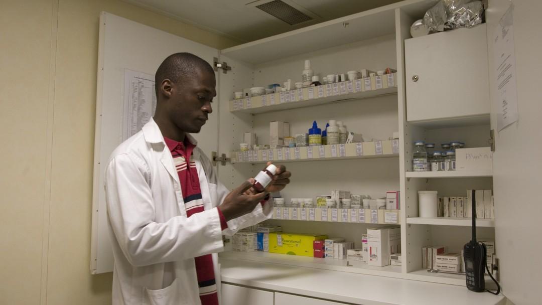 Ein afrikanischer Arzt betrachtet eine Medikamentendose, weitere Arzneimittel befinden sich im Hintergrund in einem Schrank.