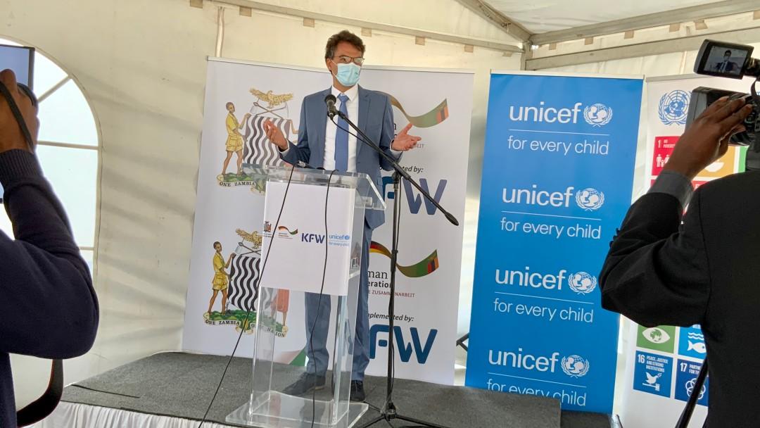 Büroleiter des KfW-Büros in Sambia, Stefan Lutz, hält eine Rede mit Mundschutz.