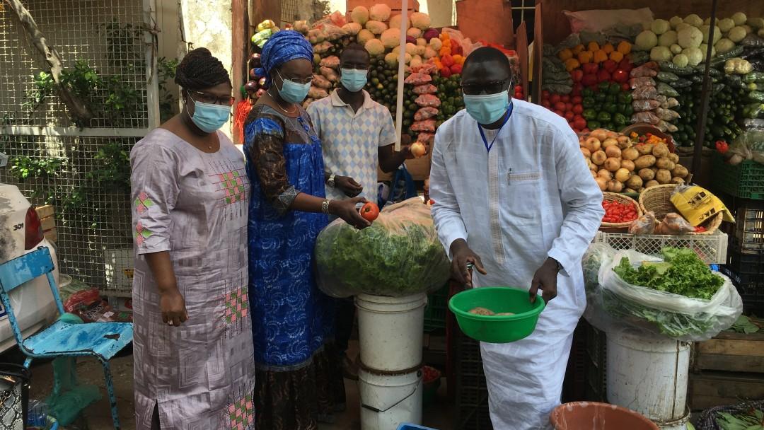 Mitarbeiterinnen des KfW Büros Dakar beim Obsteinkauf auf dem Markt. Alle tragen eine Maske.