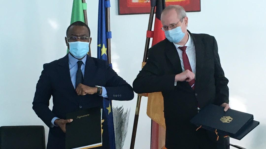 Corona-Gruß von Wirtschaftsminister Amadou Hott und Botschafter Stephan Röken; sie halten ihre Elleborgen aneinander und tragen eine Maske