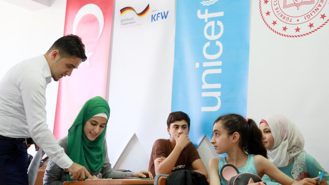 A teacher helps four Syrian refugee children in Turkey with their schoolwork.