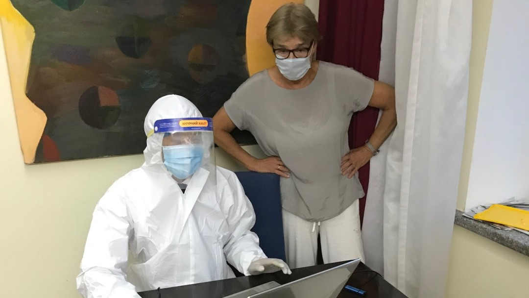 An IT specialist in protective clothing in hotel room.