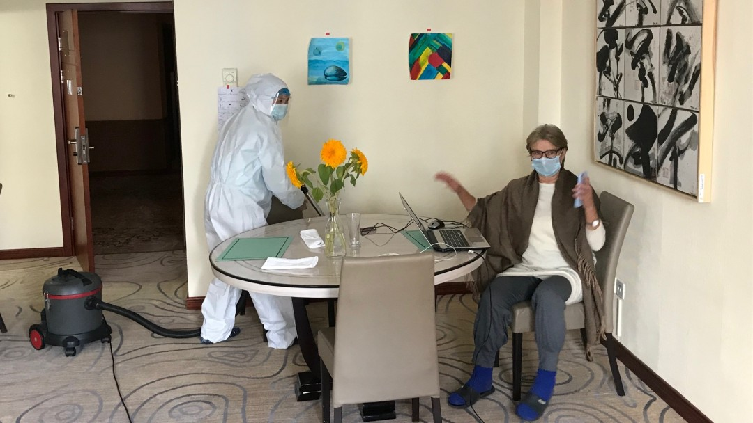 Cleaner in protective clothing in hotel room.