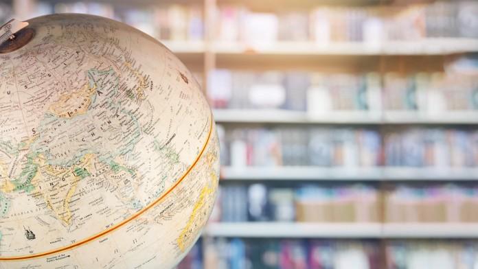 Globus im Vordergrund vor einem Bücherregal