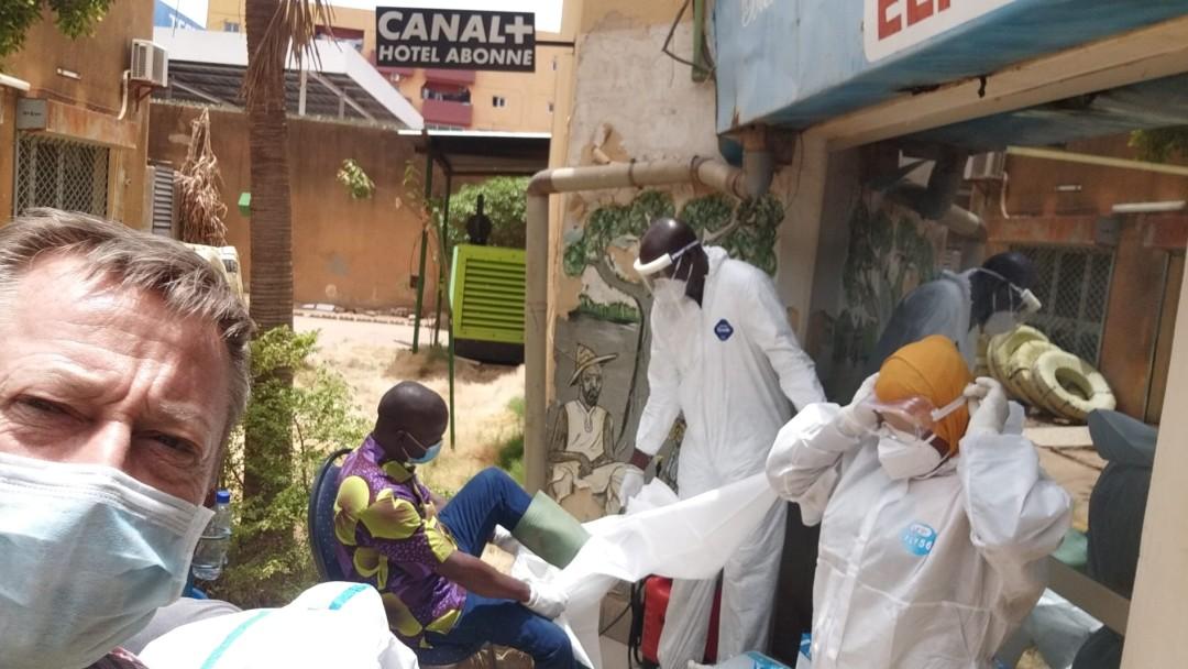 Menschen mit Mundschutz vor einem Labor