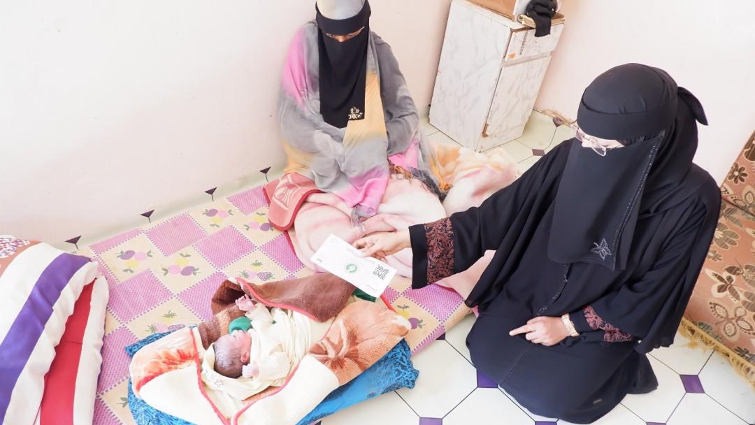 Zwei Frauen mit einem Kind und einem Gutscheinheft für sichere Mutterschaft