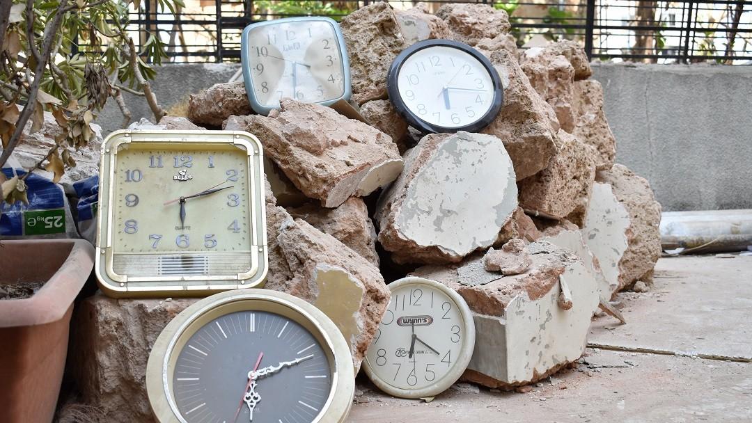 Verschiedene Wanduhren liegen auf einem Trümmerhaufen