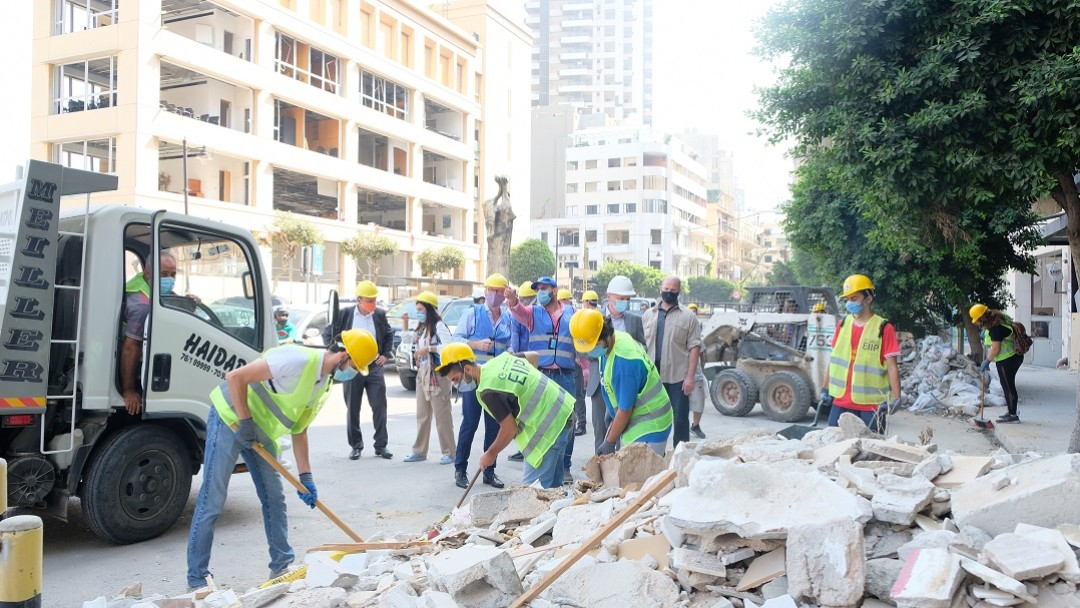 Lebanese and Syrians clear away the rubble.