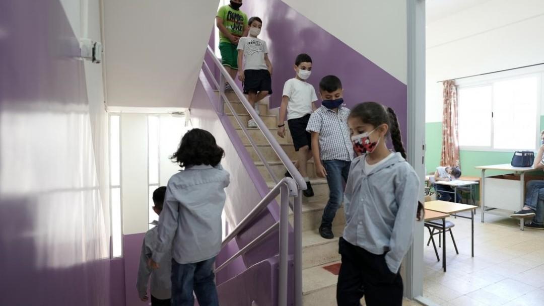 Schulkinder laufen in einem Treppenhaus nach unten