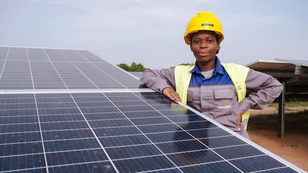 Eine Solartechnikerin steht an einer großen Solaranlage in Ghana