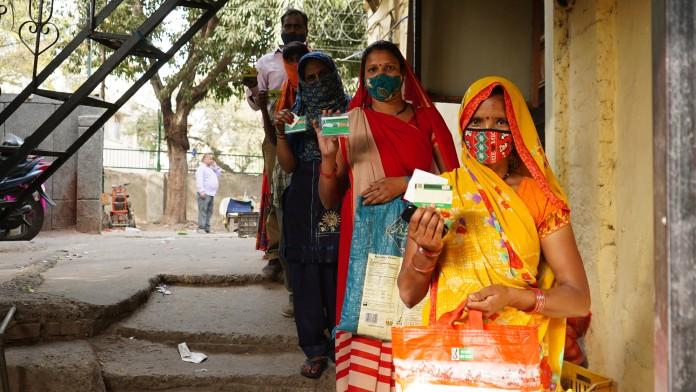 Bewohnerinnen eines Armenviertels in Delhi warten vor einen Lebensmittelgeschäft