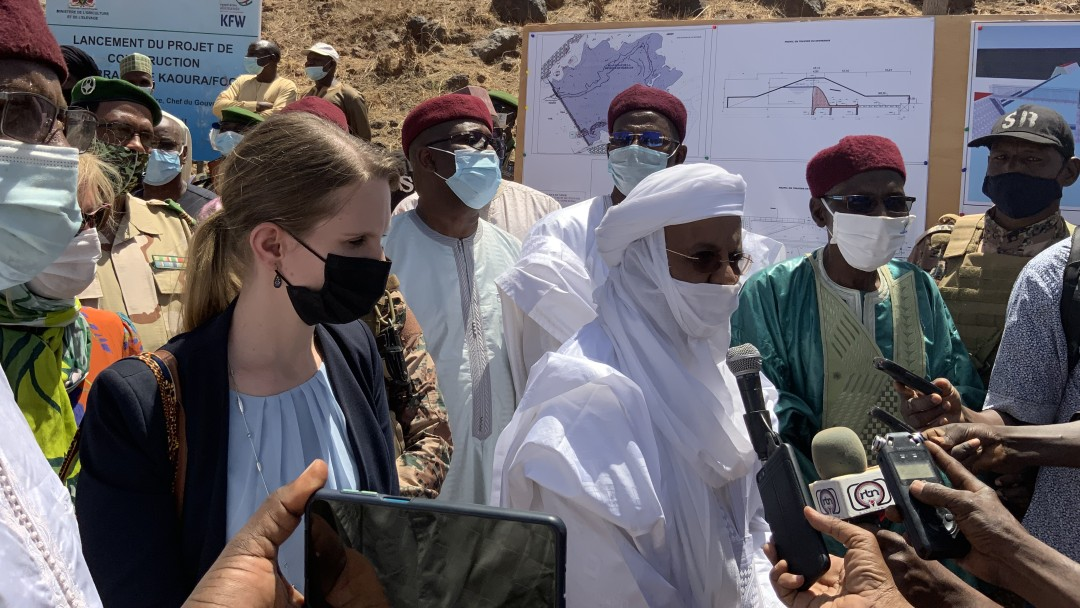 Menschengruppe vor Bauplänen, davor Hände mit Mikrofonen