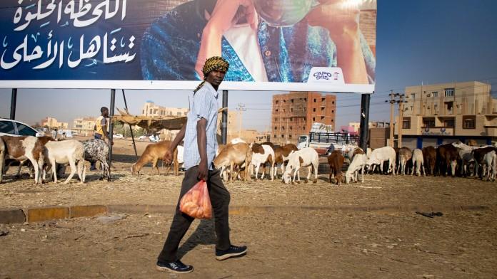 Mann läuft mit Plastiktüte durch Khartoum