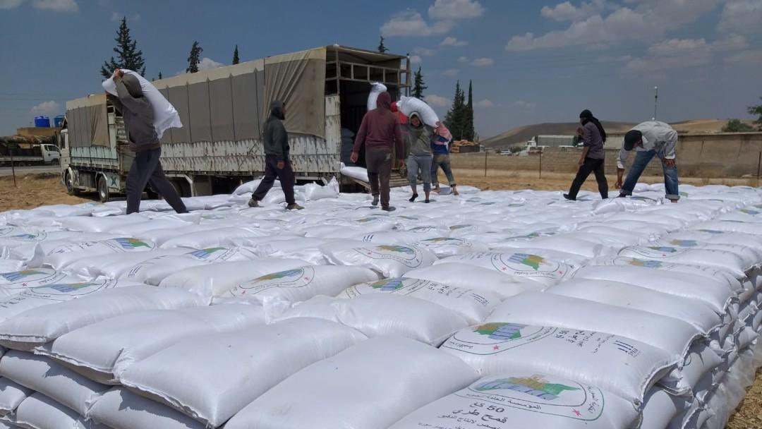 Helfer laden die gelieferten Weizenmehlsäcke aus.