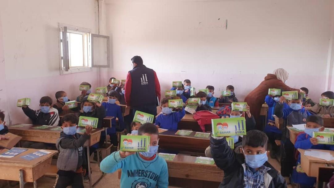 Schutzmasken werden im Klassenzimmer an die Kinder verteilt