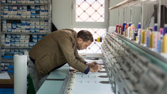 Mitarbeiter eines Stickunternehmen bei Arbeiten an einer Stickmaschine