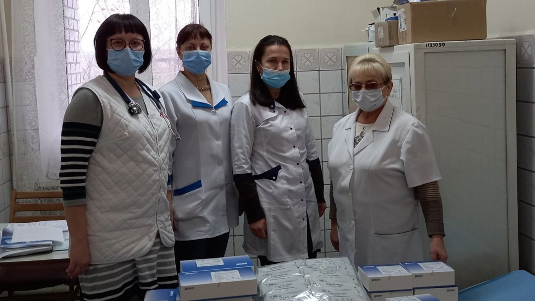 Die vier Ärztinnen und Arzthelferinnen freuen sich über eine Lieferung von COVID-19 Schnelltests.