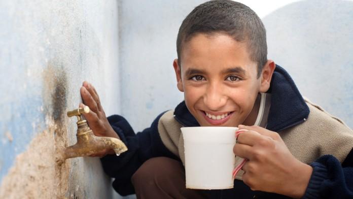 Junge trinkt aus Tasse mit sauberem Trinkwasser