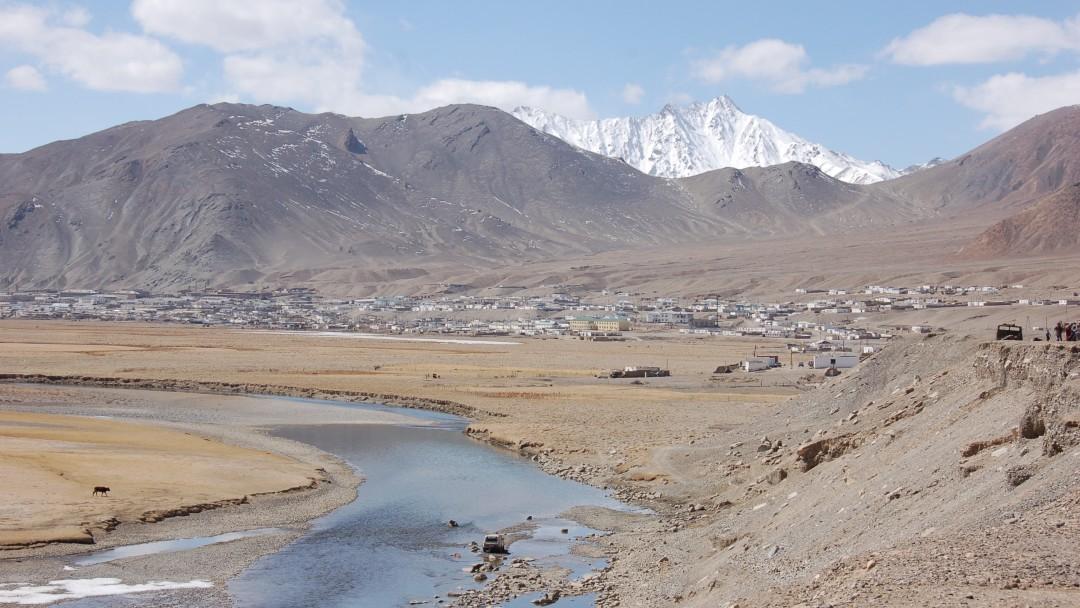 Blick auf die Stadt Murgab, am Fluss vor einem kargen Bersmassiv gelegen.