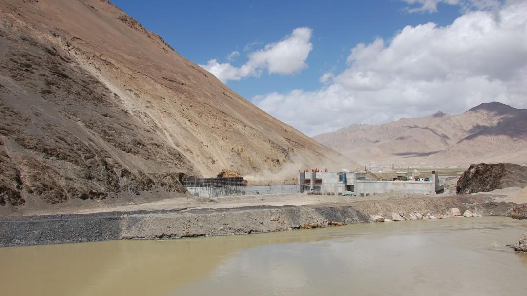 Blick auf das im Bau befindliche Wasserkraftwerk in karger Berglandschaft. Im Vordergrund fließt der Fluss.