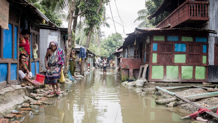 People on a flooded street in Bangladesh