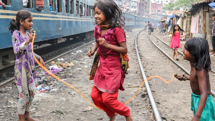 Three Indian girls skip rope between corrugated iron huts and railway tracks. A train passes by. People are standing at the open doors of the train, sitting in the windows and on the roof. Apartment blocks reach towards the sky in the background.