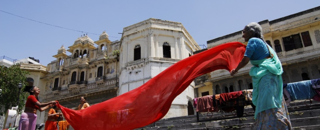 Indian women stand with a red towel on stairs