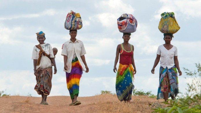 Four African women carry loads on their heads