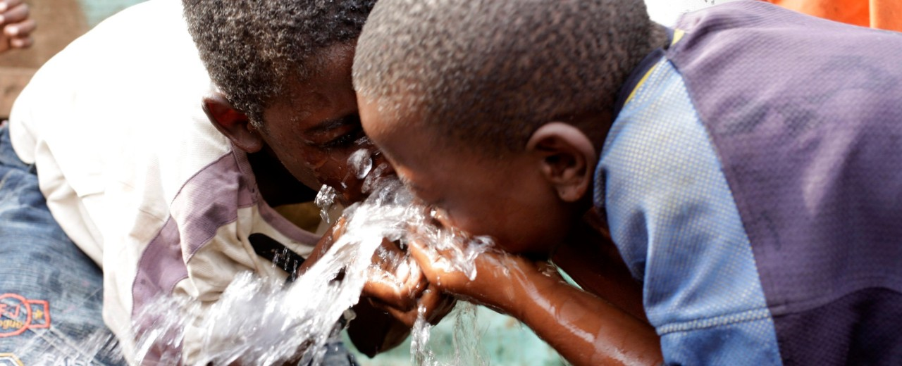 Two boys drinking water from the tab